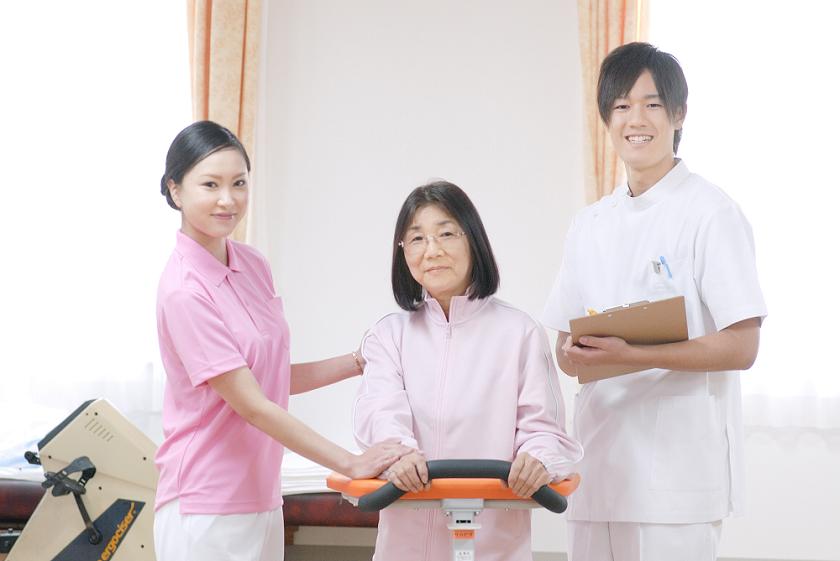 リハビリ室に立つ笑顔の男性看護師と患者と女性理学療法士