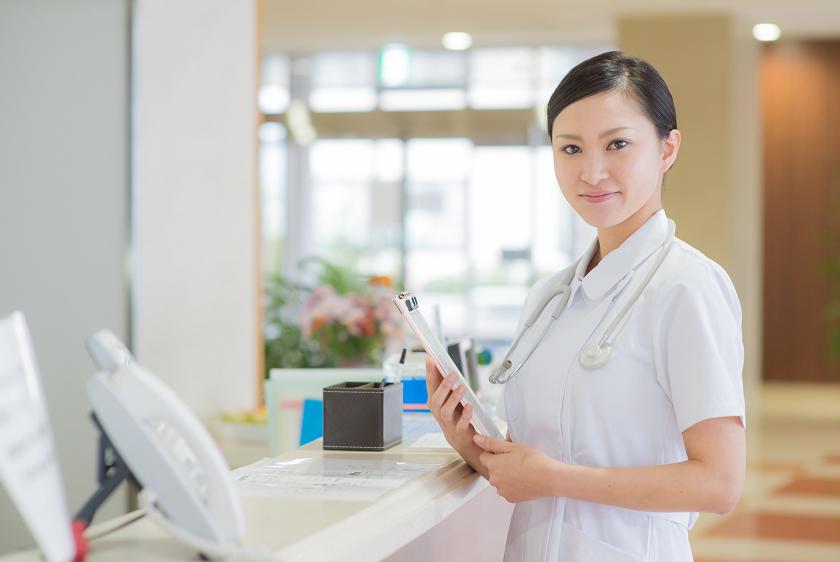 病院内でファイルを持つ若い女性看護師